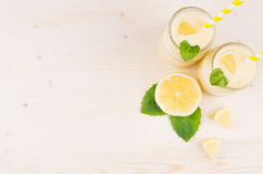 Decorative frame of yellow lemon smoothie in glass jars with straw, mint leaf, cut lemon, top view. White wooden board background, Stock Images