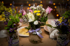 Decorative fresh bouquets of roses and wildflowers in designer bottles. Handmade. Stock Photography