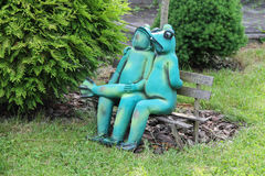Decorative funny frogs sitting on bench in city park of Schodnic Stock Image
