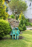 Decorative funny frogs sitting on bench in city park of Schodnic Stock Photos