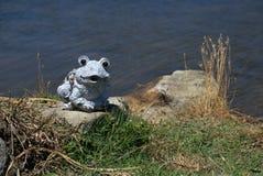 Decorative garden frog near pond. Garden accessory frog sitting on rocks. Frog statue near pond or lake Stock Photo