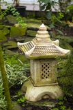 Decorative garden lantern toro in Japanese style. On the background of garden vegetation royalty free stock images