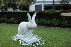 Decorative garden sculpture of a rabbit, white rabbit on a green lawn, festive decoration stock photography