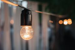 Decorative garland of old incandescent bulbs at night. Black and blur stock photos