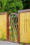 Decorative Gate in Bamboo Fence. This lovely bamboo wall and decorative gate is the entrance to a peaceful, Buddhist themed zen garden royalty free stock images