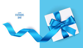 Decorative gift box with blue bow and long ribbon. Happy Father`s Day text. Father`s Day template with gift box and blue bow Royalty Free Stock Image