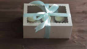 Decorative gift box tied with cupcakes a turquoise ribbon in female hands