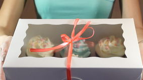 Decorative gift box tied with cupcakes a turquoise ribbon in female hands stock footage