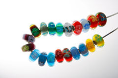 Decorative Glass Beads on Cord. Glass beads decorated with flowers strung on a cord Stock Image