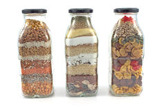Decorative glass bottles with seeds. Isolated on white Stock Photography