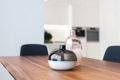 Decorative glass vases on wooden table in the kitchen. royalty free stock image