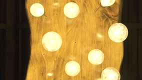 Decorative glowing bulbs hanging on ceiling in dark room. Lighting lamp from vintage bulbs in modern interior decor. Retro tungsten light bulb on room ceiling stock footage