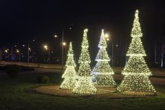 Decorative glowing christmas trees on celebration Christmas and New Year. Festive decorations in night city before Holidays. Xmas background with shining royalty free stock photos