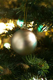 Decorative gold bauble in a Christmas tree Royalty Free Stock Photos