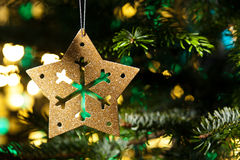 Decorative Gold star ornament in a Christmas tree Stock Photo