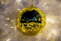 Decorative golden balls hanging on a Christmas tree. With a white needle. Yellow balls on Christmas tree illuminated from LED bulbs on chain Stock Photography