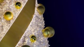 Decorative golden balls with ribbon hanging on a Christmas tree. With a white needle on dark blue background. Yellow balls on Christmas tree illuminated from Royalty Free Stock Photo