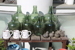 Decorative green bottles. Decorative bottles of green glass and ceramic pots for plants Royalty Free Stock Image