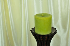Decorative green candle with silk background Royalty Free Stock Photos