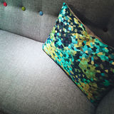 Decorative green and yellow cushion on a sofa Stock Photos