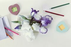 Decorative greeting composition of the inscription be happy, irises, pencils, empty notebooks on the table. Top view stock images