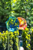 Decorative, hand-made glass flowers. Garden decorations. Flowers with petals resembling trumpets, hand made of colored glass Royalty Free Stock Photography