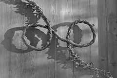 Decorative handle of twisted metal wires on a wooden door (monochrome) Stock Photos