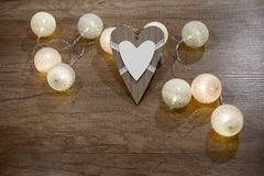 Decorative handmade heart and lights on the wooden table. Decorative wooden heart and multicolored lights on the wooden table Stock Images