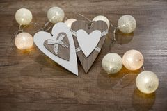 Decorative handmade hearts and lights on the wooden table. Decorative wooden hearts and multicolored lights on the wooden table Royalty Free Stock Photo