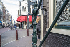 Decorative handrail in the streets of Amsterdam with blurry red venetians in the background Stock Image