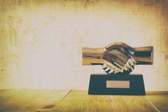 Decorative handshake gadget over wooden table. business concept Stock Photos