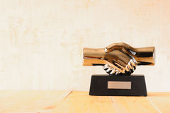 Decorative handshake gadget over wooden table. business concept Stock Photos