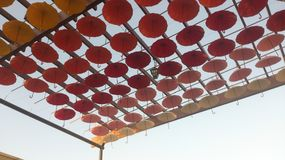Decorative hanging. Diagonal composition made of red orange and white hanging umbrellas Stock Images