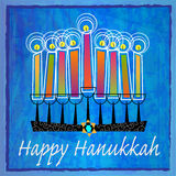 Decorative Hanukkah Greetings. Stylized menorah with colorful candles and Happy Hanukkah text on blue abstract background. Eps10