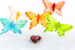 Decorative heart and butterflies in white snow. Purple decorative heart in the white snow on the background of  multicolored decorative butterflies close up. The Stock Image