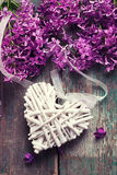 Decorative heart and fresh lilac flowers on green aged wooden ba Royalty Free Stock Image
