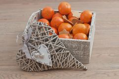 Decorative heart and gingerbread with tangerine. Decorative heart with box of mandarins and gingerbread on the background stock image