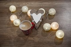 Decorative heart, lights and cup of coffee on the wooden table. Decorative wooden heart, multicolored lights and red cup of coffee with milk on the wooden table Royalty Free Stock Images