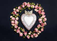 Decorative heart with round frame of small dry roses on black background. Place for text. Royalty Free Stock Photos