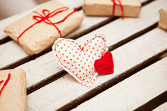 Decorative hearts and gift boxes on white wooden background Stock Photos