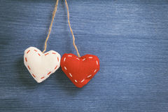 Decorative hearts hanging on the rope against blue wood wall Stock Photos