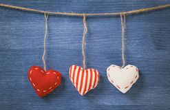 Decorative hearts hanging on the rope against blue wood wall Royalty Free Stock Photo