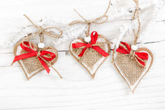 Decorative hearts on snow-covered branch on wooden background Royalty Free Stock Images