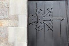 Decorative hinge. Dark wood and decorative hinge on door of stone building Royalty Free Stock Image