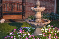 Decorative home water fountain in a bed of flowers royalty free stock image