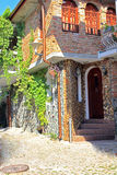 Decorative house. The house in the street of the old town. Porch of the house is decorated with round river stone. The construction of a house of the last stages Royalty Free Stock Photo