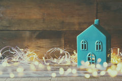 Decorative house next to gold garland lights on wooden background. copy space Royalty Free Stock Images