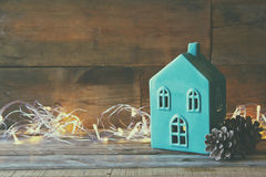 Decorative house next to gold garland lights on wooden background. copy space Stock Image