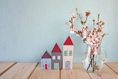 Decorative house next to white spring flowers. selective focus Royalty Free Stock Image