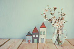 Decorative house next to white spring flowers. selective focus. vintage filtered and toned Stock Images